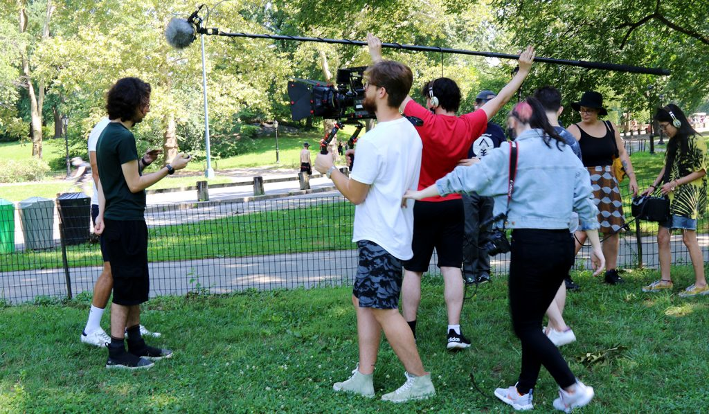 Students working as a film crew, directing, operating the camera and recording sound at Central Park in New York.
